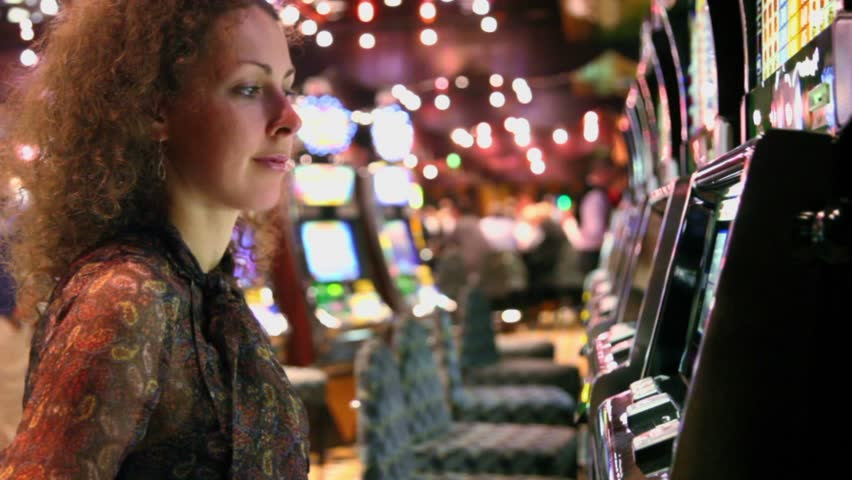 Woman pushes buttons on play machine in casino and becomes very happy when she wins