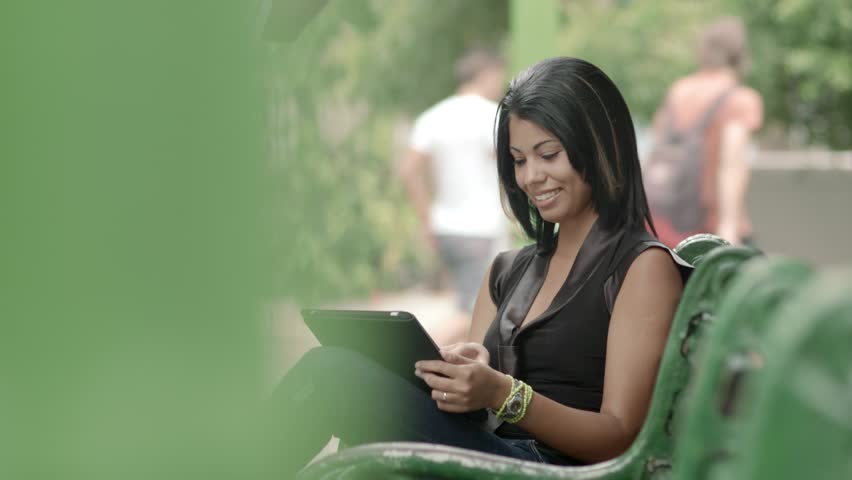 Portrait of happy young hispanic woman typing on digital tablet computer and sitting on bench in city park - HD stock video clip