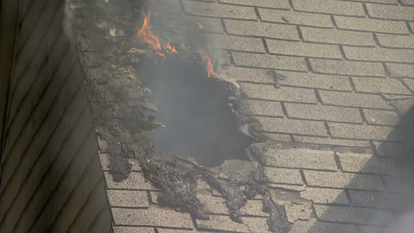 Smoke and fire pouring out of hole in roof of house on fire