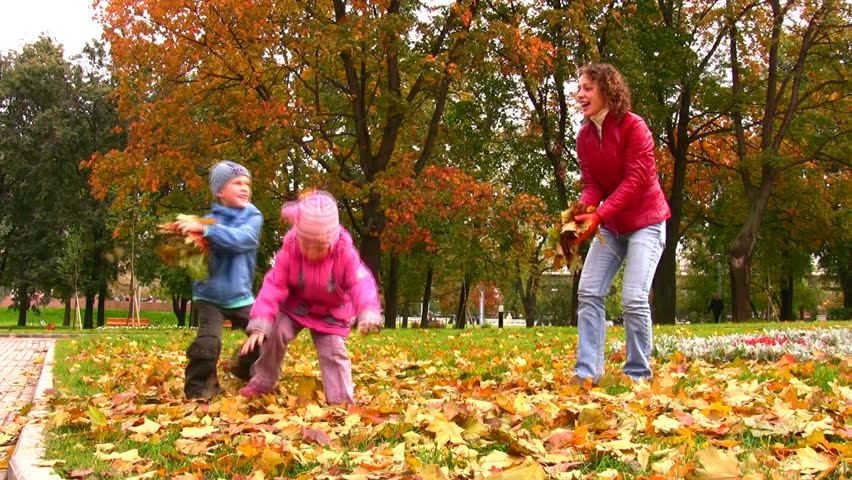 mother with children throw autumn leaves  - HD stock footage clip