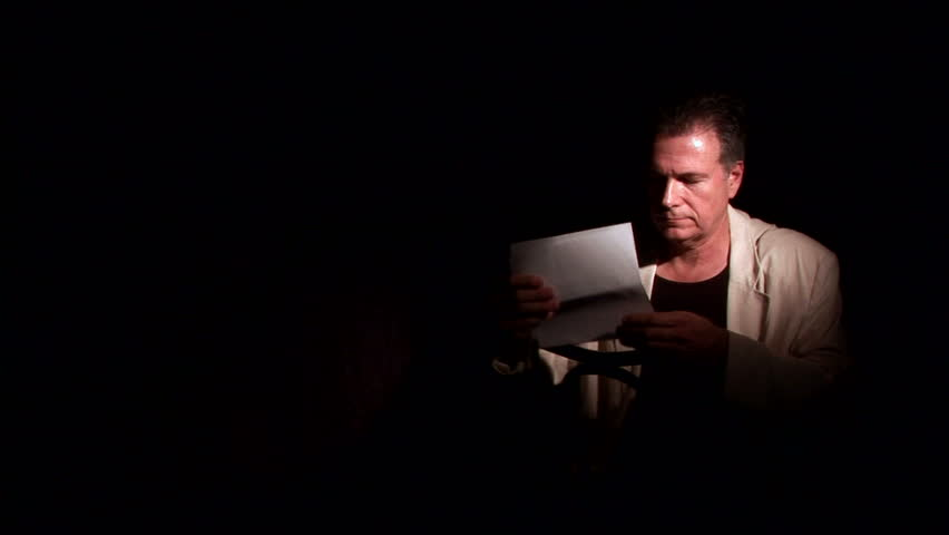 A troubled man, reading a letter or notice, sitting astride a chair in a dark room. - HD stock footage clip