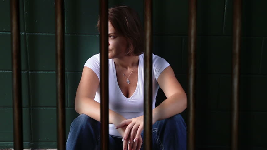 Depressed Female Sitting In Jail Cell