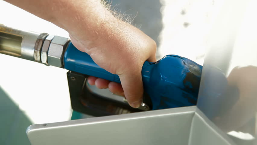 Close-up of a man's hand using a petrol pump to fill his car up with fuel