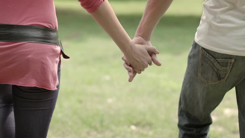 Romantic young people and love, man and woman as male and female college students walking and holding hands in city park. Tilt shot, slow motion - HD stock video clip