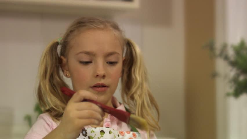 Girl brushing cinnamon bun with beaten egg