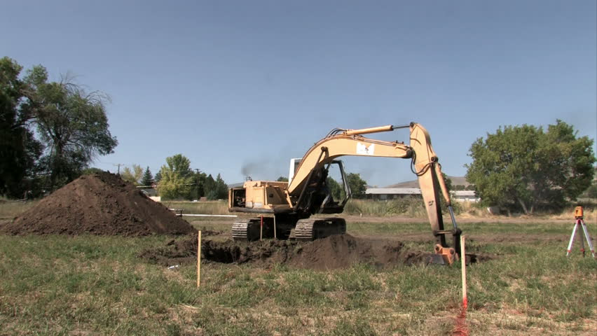 SANPETE COUNTY, UT - SEPT 16: backhoe excavator machine digging a basement for a new house or home. Located in the middle of a farm field. Construction slowdown but not stop. - HD stock footage clip