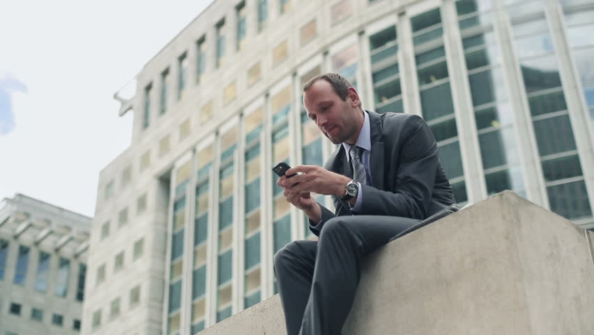 Young handsome businessman with smartphone in the city