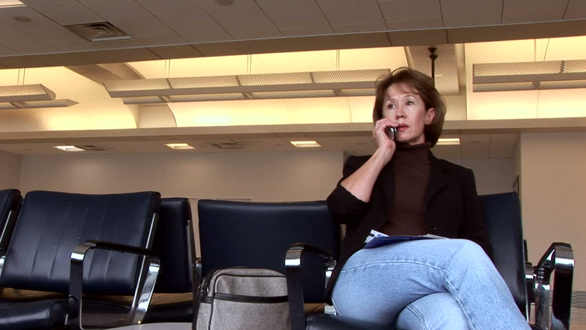 A woman sitting in an airport talking on a cell phone.  - HD stock footage clip