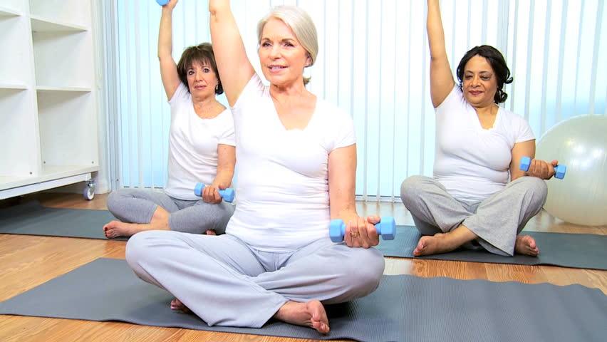 Senior Caucasian female instructor teaching muscle stretching to senior ladies