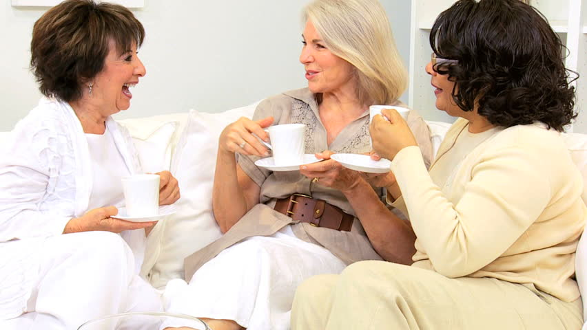 Three retired multi ethnic girlfriends visiting drinking coffee home - HD stock footage clip