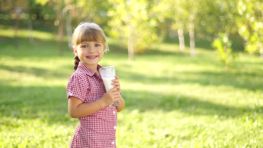 Girl drinking milk outdoors. Thumbs up. Ok.