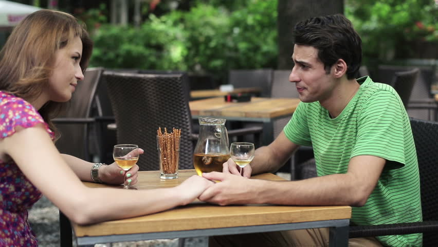 Couple drinking wine and holding hands in cafe - HD stock footage clip