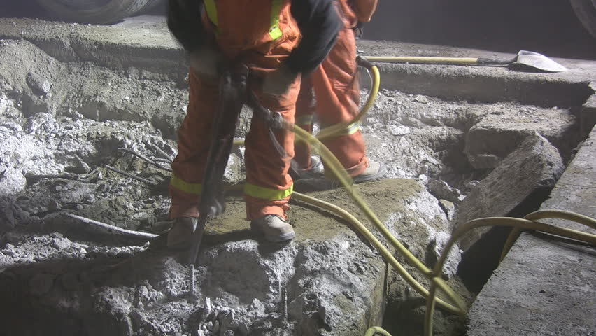 Jackhammers. Good audio. Wide shot. Road crew working at night under bright lights.