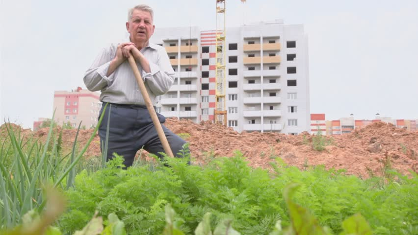 Old man abuts on spades handle and speak about construction site behind