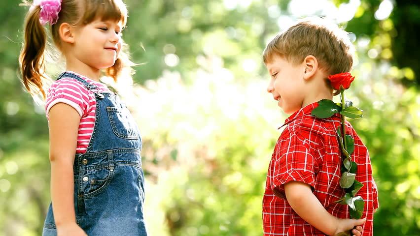 Two children speaking and boy present flower