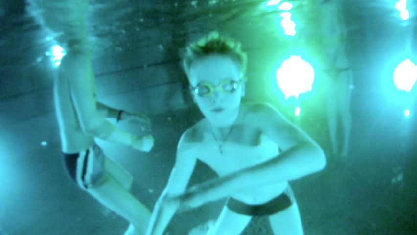 Boy swims under water in pool with swimming goggles