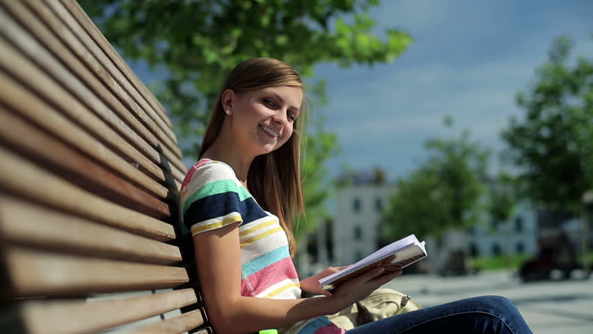 Happy female student reading book in the city, stabilized shot - HD stock footage clip