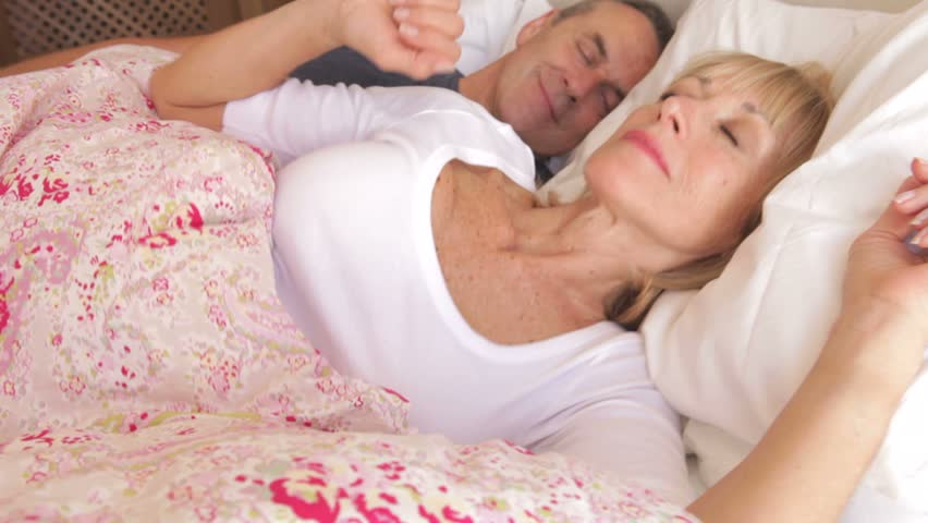 Camera tracks along bed to sleeping senior couple as woman stretches,open eyes and looks at camera. - HD stock footage clip