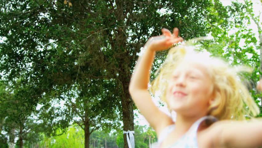 Cute little blonde girl jumping for joy in sunshine in home garden - HD stock video clip