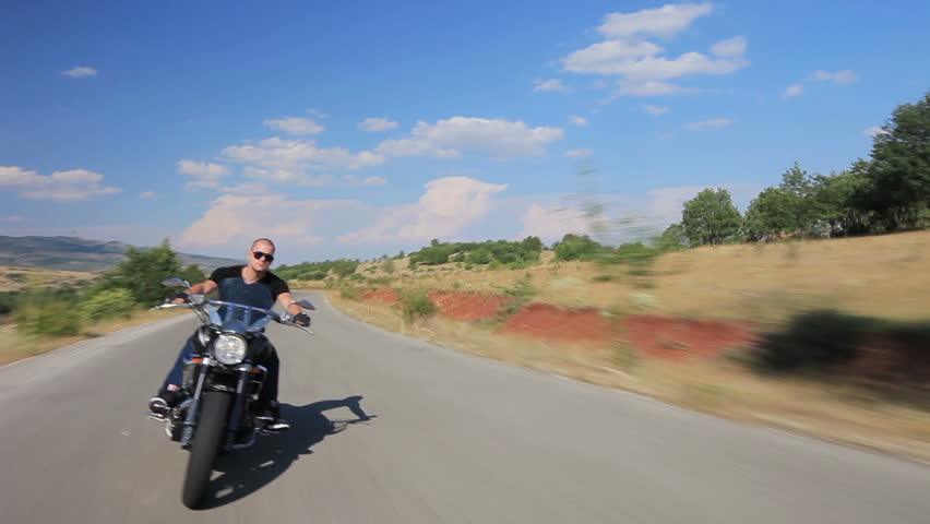 A biker riding a customized motorcycle on an open road - HD stock footage clip