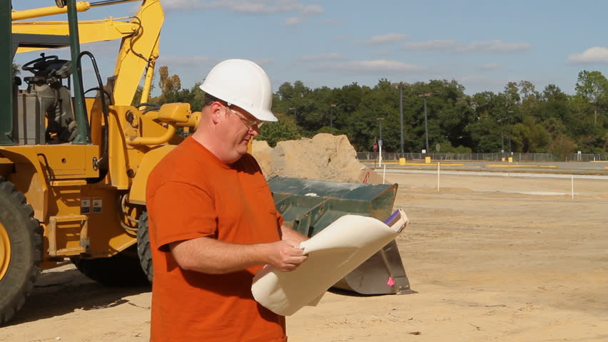 Contractor holding blueprints at an excavation site stands in front of a bulldozer and surveys the construction progress. - HD stock video clip