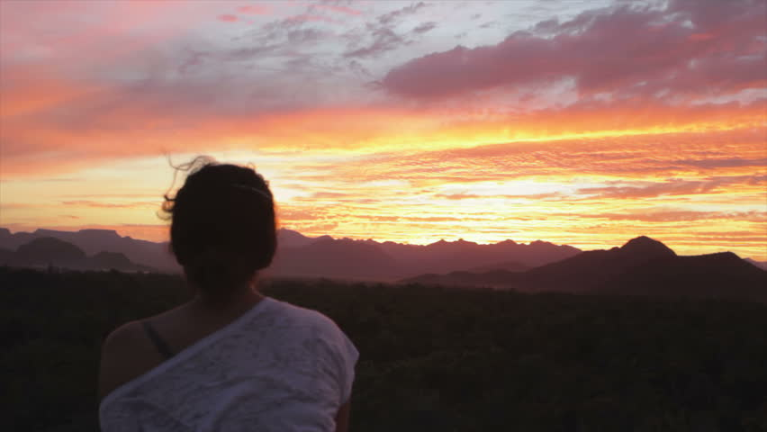 Woman watching sunset over the mountains in Baja California, Mexico
