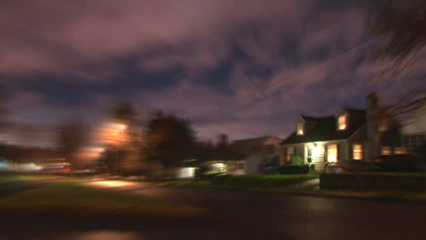 Night time lapse in residential neighborhood with person running in super speed effect.