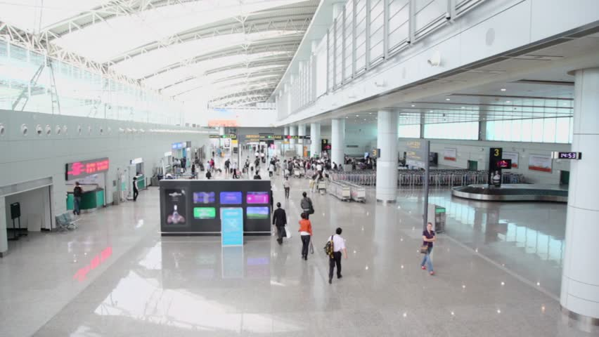 Passengers walk with luggage in airport, shown in motion