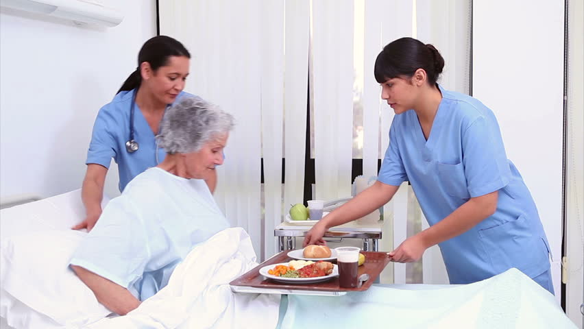 Nurse bringing food to a senior patient in a hospital room - HD stock video clip