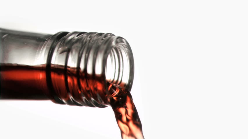 Close up, red liquid in a super slow motion flowing of the glass bottleneck against a white background - HD stock footage clip