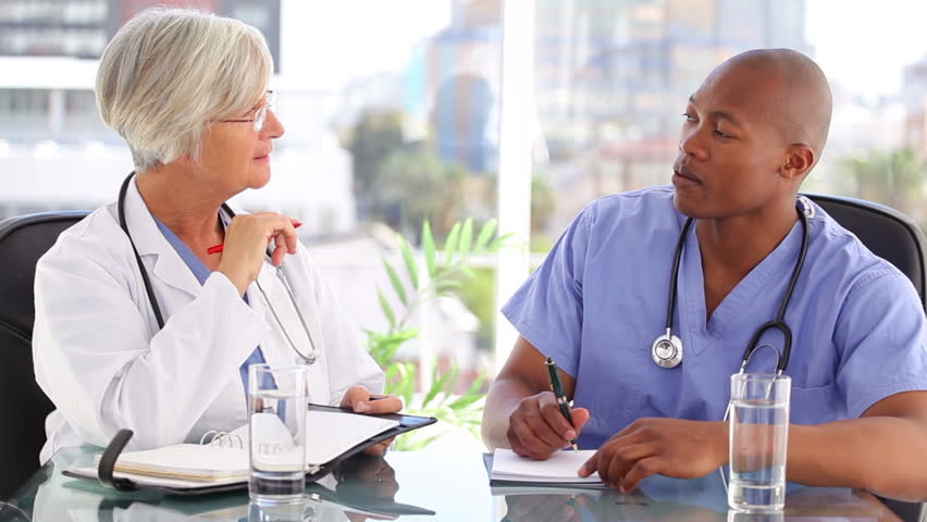 Nurse and doctor writing while working together in a bright room - HD stock video clip