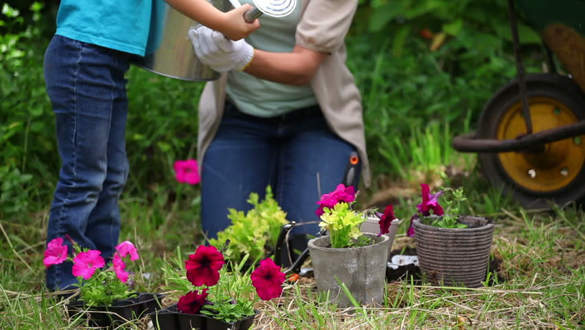 Mother and daughter watering flowers together in a garden