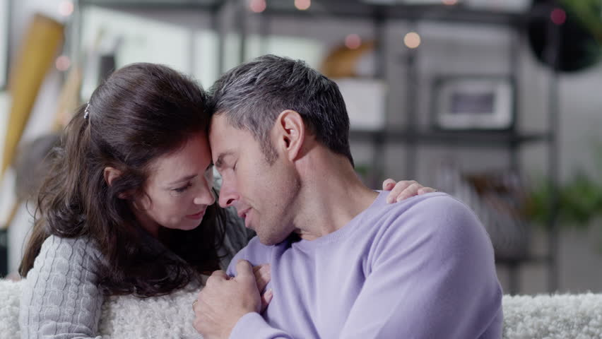 A man who is concerned and upset is comforted by his wife - HD stock footage clip