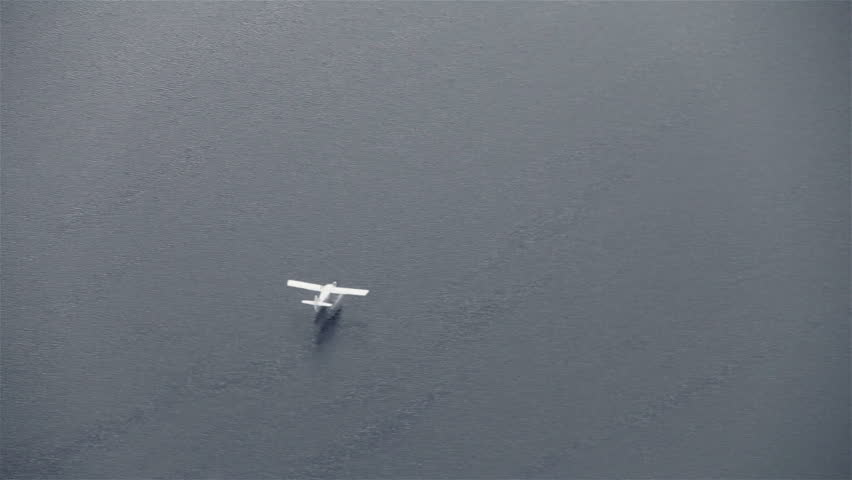 View from airplane of float plane on lake water approaching and landing - HD stock footage clip