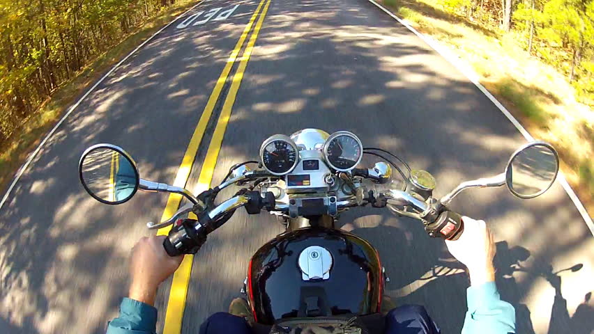 A shot of the handlebars, gages and gas tank of a speeding motorcycle as seen from a high angle helmet cam.