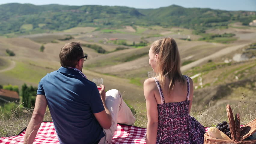 Young couple in love drinking wine on picnic, crane shot