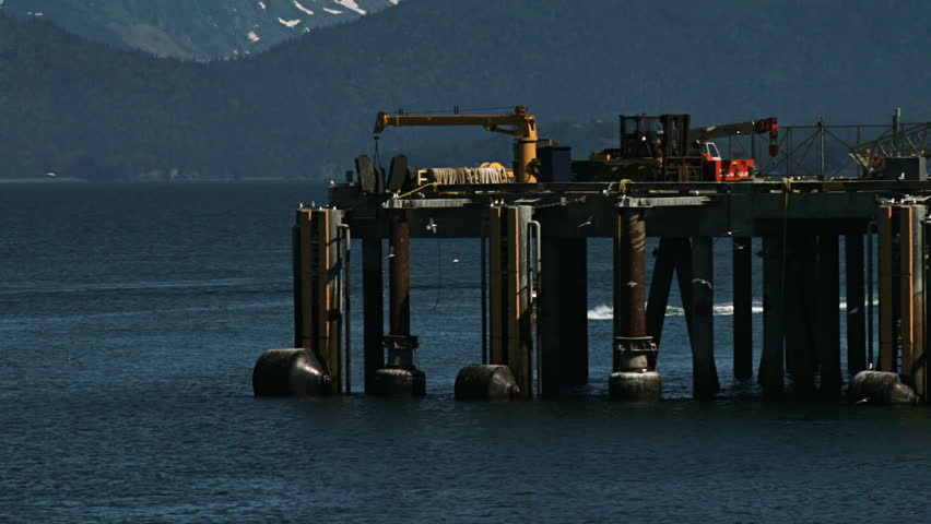 A power boat motors past the ferry and industrial dock at Land's End on the Homer Spit in Homer, Alaska.