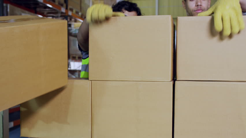Warehouse workers in high visibility clothing taking plain brown boxes off of a pallet to store elsewhere
