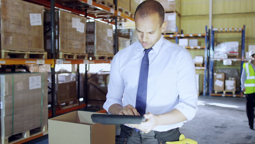 A young man is working in a warehouse with a digital tablet, he is dressed in a shirt and tie. He gives instructions to a female worker and another employee can be seen working in the background