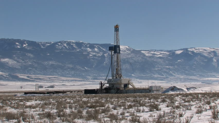 Oil rig in a valley of Utah near mountain. Blue sky and snow of winter. - HD stock video clip