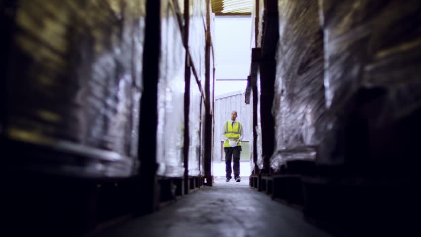 A male industrial worker walks down a narrow aisle in between two rows of goods in a warehouse. He puts on his hard hat as he enters from the daylight behind him. Low angle and slow motion.
