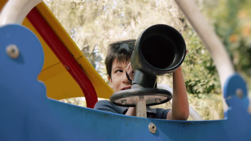 Hispanic Boy Playing with Toy Spyglass at Public Park.