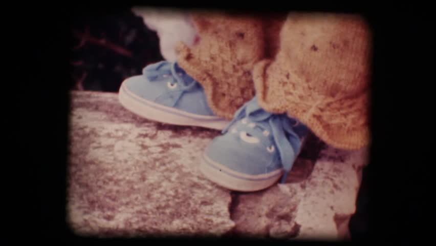 Vintage 8mm. Original footage digitalized. Shoes of a little baby trying his first steps