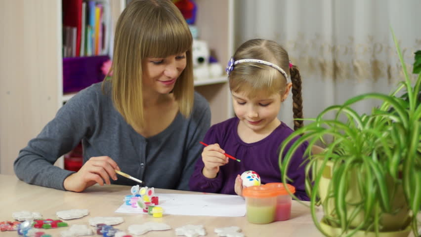Mother and child decorate an Easter egg. Looking at camera - HD stock footage clip