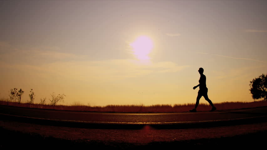 a person power walking against sunset
