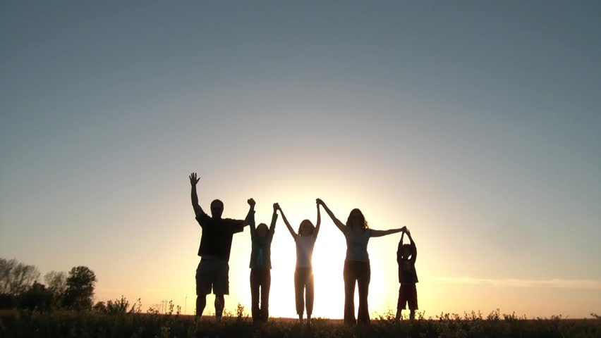 Group of five people holds hands, and then raises arms in unity backlit by large sunset in background, on a hill in summer. Silhouettes with copyspace.