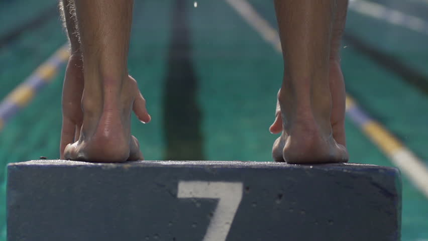 Slow-Motion Shot Of A Professional Male Swimmer Jumping Off The Starting Block Into The Pool.