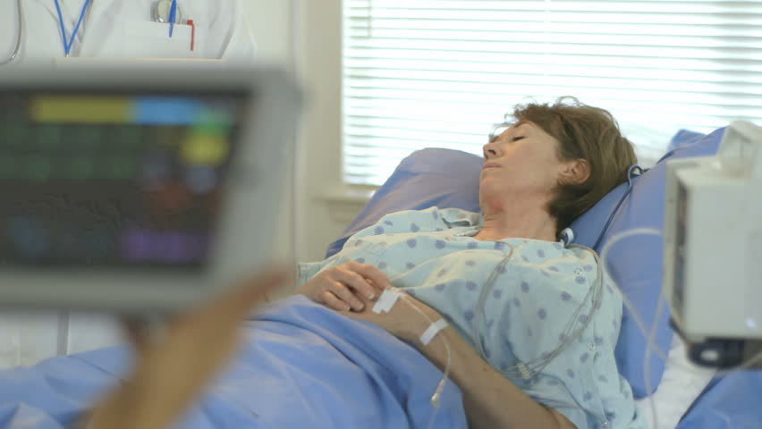 Camera rack focuses from a portable patient monitor held by a doctor to a mature woman lying in a hospital bed. - HD stock video clip