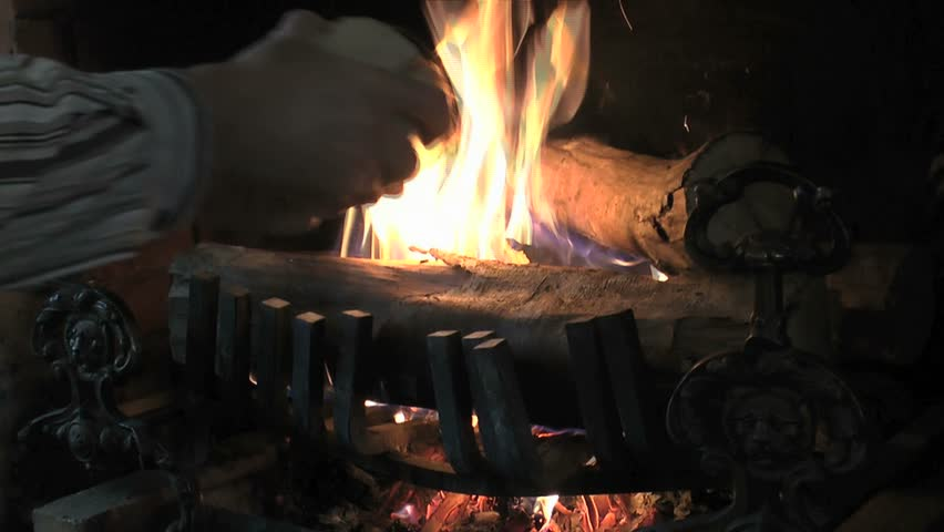 Man places several logs in fire roaring in home fireplace. 1080p - HD stock video clip