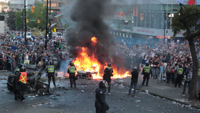 VANCOUVER, CANADA - JUNE 15 Police and crowd yelling as car burns during the 2011 Vancouver Stanley Cup riot on June 15, 2011. The 2011 Vancouver Stanley Cup riot was a public disturbance that broke out in downtown Vancouver, BC, Canada on Wed, June 15, 2 - HD stock video clip